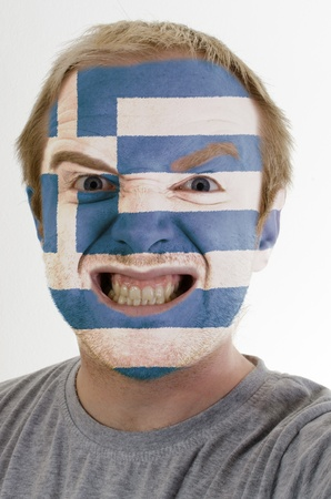 High key portrait of an angry man whose face is painted in colors of greece flag photo