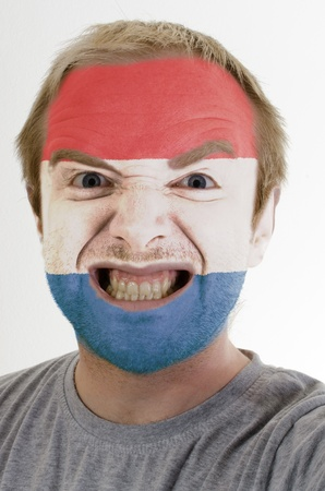 High key portrait of an angry man whose face is painted in colors of holland flag photo
