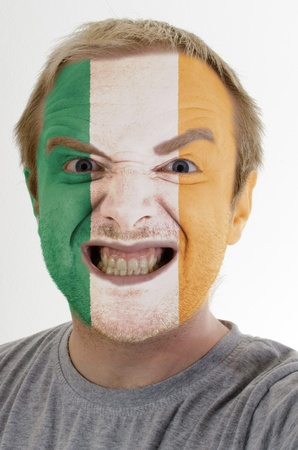 High key portrait of an angry man whose face is painted in colors of ireland flag photo
