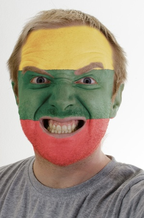 whose: High key portrait of an angry man whose face is painted in colors of lithuania flag Stock Photo