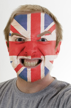 whose: High key portrait of an angry man whose face is painted in colors of united kingdom flag