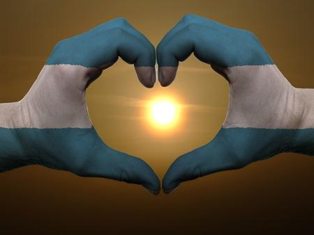 el salvador flag: Gesture made by el salvador flag colored hands showing symbol of heart and love during sunrise