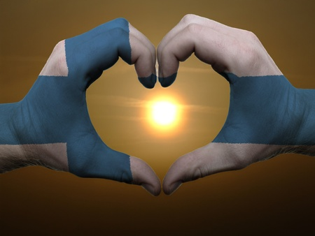 made in finland: Gesture made by finland flag colored hands showing symbol of heart and love during sunrise