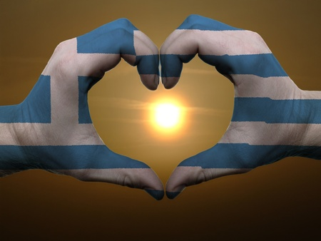 Gesture made by greece flag colored hands showing symbol of heart and love during sunrise