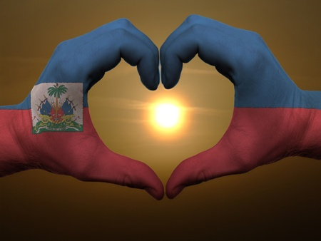 haiti: Gesture made by haiti flag colored hands showing symbol of heart and love during sunrise Stock Photo