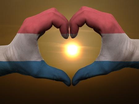 drapeau hollande: Geste effectu� par les mains du pavillon holland en couleurs montrant le symbole du c?ur et de l'amour au lever du jour