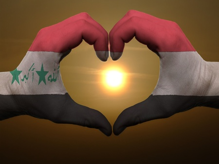 Gesture made by iraq flag colored hands showing symbol of heart and love during sunrise photo