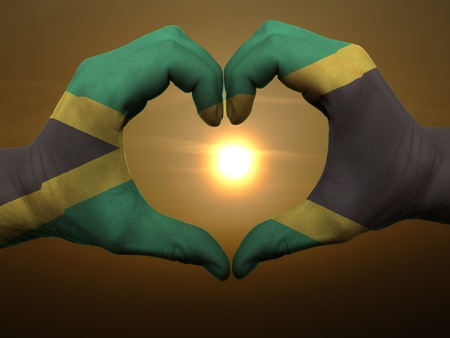 jamaican: Gesture made by jamaica flag colored hands showing symbol of heart and love during sunrise