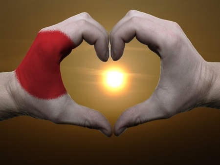 Gesture made by japan flag colored hands showing symbol of heart and love during sunrise photo