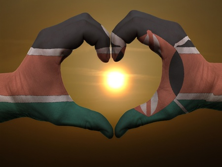 Gesture made by kenya flag colored hands showing symbol of heart and love during sunrise Stock Photo - 11159039