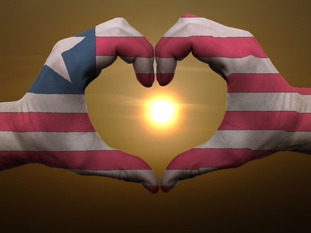 Gesture made by liberia flag colored hands showing symbol of heart and love during sunrise photo