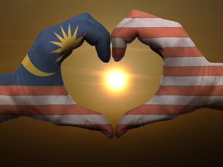 Gesture made by malaysia flag colored hands showing symbol of heart and love during sunrise photo
