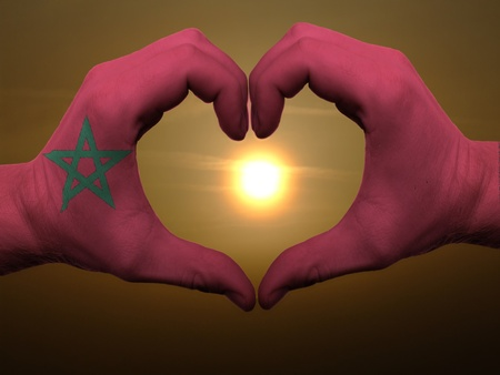 made in morocco: Gesture made by morocco flag colored hands showing symbol of heart and love during sunrise