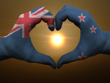 bandera de nueva zelanda: Gesto hecho por Nueva Zelanda manos la bandera de colores que muestra el s�mbolo del coraz�n y el amor durante el amanecer Foto de archivo