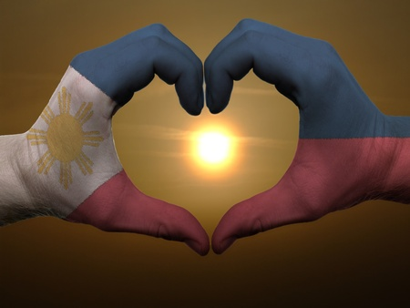 Gesture made by phillipines flag colored hands showing symbol of heart and love during sunrise photo