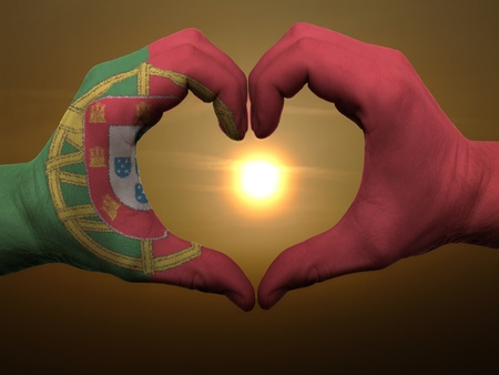 Gesture made by portugal flag colored hands showing symbol of heart and love during sunrise photo