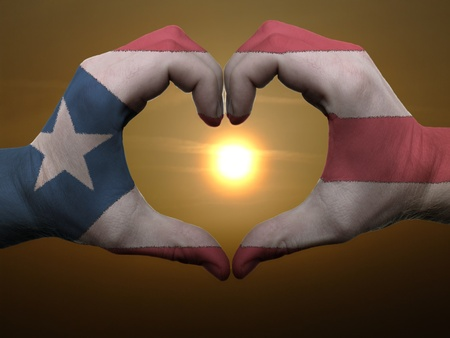 Gesture made by puertorico flag colored hands showing symbol of heart and love during sunrise