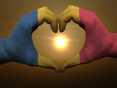 Gesture made by romania flag colored hands showing symbol of heart and love during sunrise photo