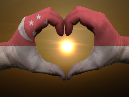 singaporean flag: Gesture made by singapore flag colored hands showing symbol of heart and love during sunrise