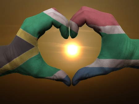 south africa flag: Gesture made by south africa flag colored hands showing symbol of heart and love during sunrise Stock Photo