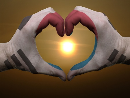 Gesture made by south korea flag colored hands showing symbol of heart and love during sunrise photo