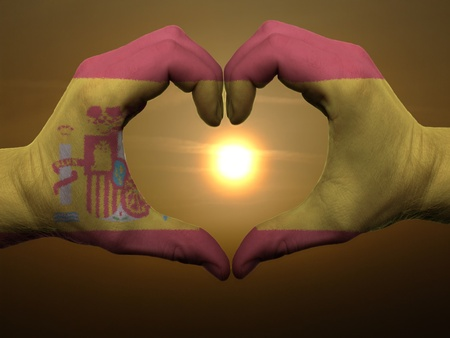 flag spain: Gesture made by spain flag colored hands showing symbol of heart and love during sunrise Stock Photo