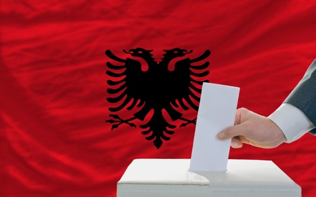 man putting ballot in a box during elections in albania photo