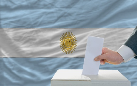 man putting ballot in a box during elections in argentina photo