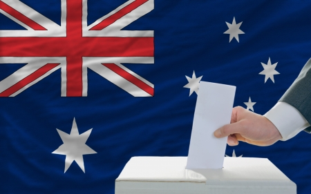 electorate: man putting ballot in a box during elections in australia