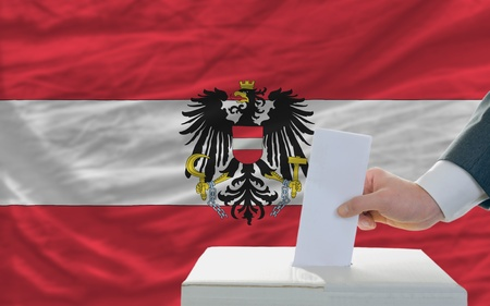 parliamentary: man putting ballot in a box during elections in austria
