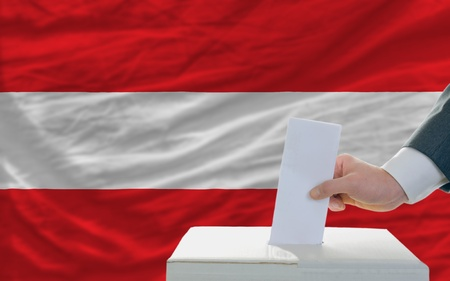 man putting ballot in a box during elections in austria photo