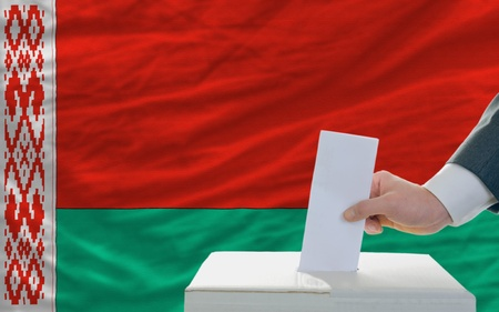 man putting ballot in a box during elections in belarus photo