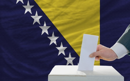 man putting ballot in a box during elections in bosnia herzegovina photo