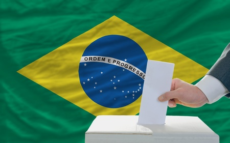 man putting ballot in a box during elections in brazil photo