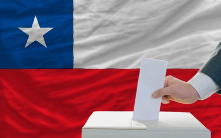 man putting ballot in a box during elections in chile photo