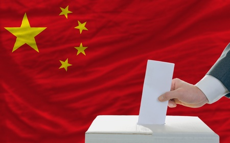 electorate: man putting ballot in a box during elections in china