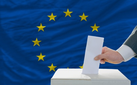 man putting ballot in a box during elections in european union photo