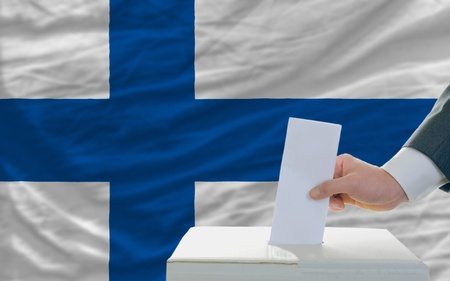 parliamentary: man putting ballot in a box during elections in finland