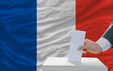 man putting ballot in a box during elections in france