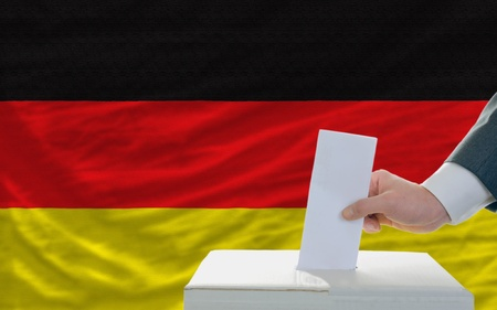 man putting ballot in a box during elections in germany Stock Photo