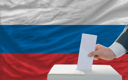 man putting ballot in a box during elections in russia photo