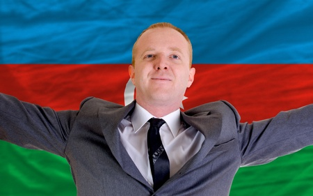 azerbaijanian: joyful investor spreading arms after good business investment in azerbaijan, infront of flag
