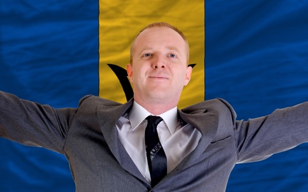 joyful investor spreading arms after good business investment in barbados, in front of flag Stock Photo - 11284217