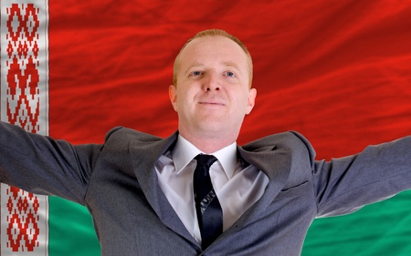 spreading arms: joyful investor spreading arms after good business investment in belarus, in front of flag Stock Photo