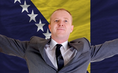joyful investor spreading arms after good business investment in bosnia herzegovina, in front of flag photo