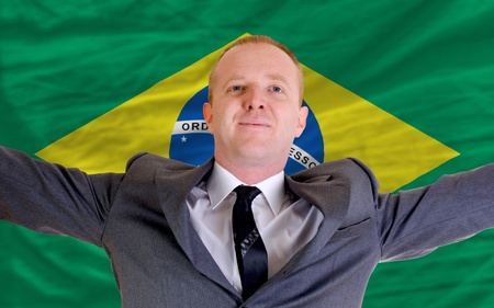 spreading arms: joyful investor spreading arms after good business investment in brazil, in front of flag Stock Photo