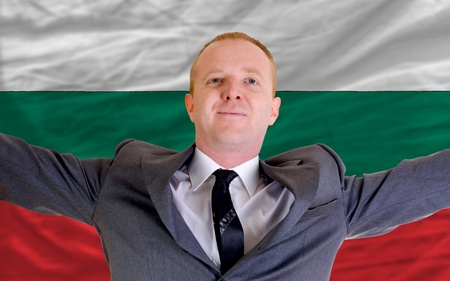 joyful investor spreading arms after good business investment in bulgaria, in front of flag photo