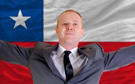 bandera chilena: inversor alegre difusión de armas después de la inversión un buen negocio en Chile, delante de la bandera