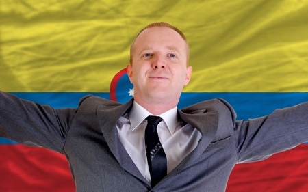 spreading arms: joyful investor spreading arms after good business investment in columbia, in front of flag Stock Photo