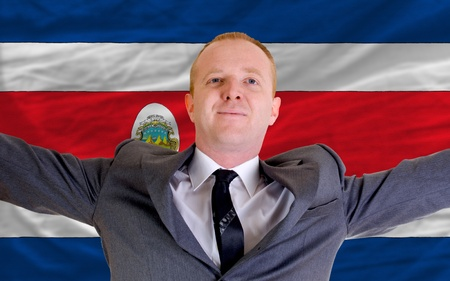 joyful investor spreading arms after good business investment in costarica, in front of flag Stock Photo - 11284218